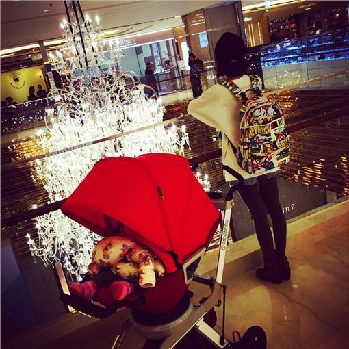 照片中,除了坐在婴儿推车中的女儿外,一旁背著后背包的背影「少女」