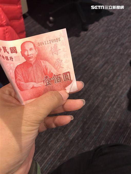 百元鈔右下角遭撕開模樣。