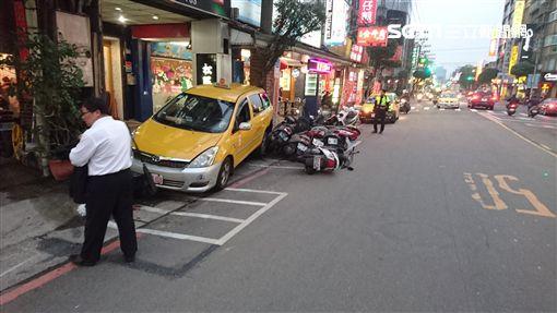 傅姓計程車司機行經中央路時,先追撞前方機車騎士後,倒車時暴衝再撞上路旁10輛機車(翻攝畫面)