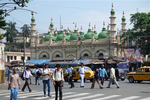 印度少數假日,必須由寺廟的祭司或清真寺的教士「觀天象」,看月亮圓不圓,再由政府公告隔天是否放假。圖為加爾各答一間清真寺前繁忙的街道。(檔案照片)中央社記者康世人加爾各答攝 106年4月20日