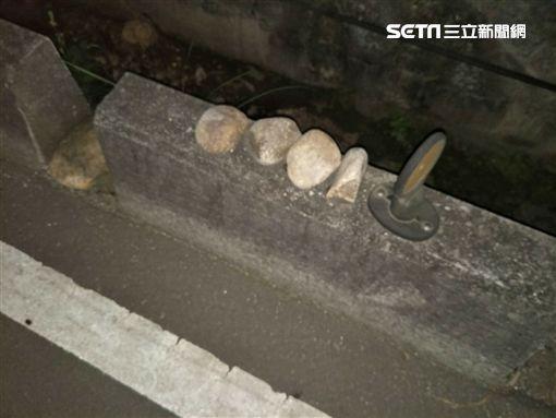 事後警方在馬路中央撿到4顆周男所堆放的石頭。(圖/翻攝畫面)