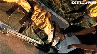 林女疑因心情不好走入淡水河輕生,卻因退潮而卡在淤泥裡,警消獲報後將她救出送醫救治(翻攝畫面)
