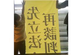 民主鬥陣成員困在房間,透過窗戶向外貼海報。(圖/翻攝民主鬥陣臉書)