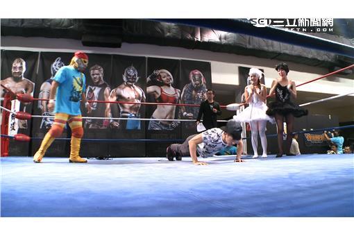 (圖二)JR上擂台時依然敬業的演出,以英雄救美之姿前往搭救受困中的兩位女主持。