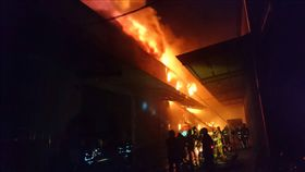新北市泰山區楓江路46巷1處連棟鐵皮建築物,25日晚間6時30分許發生火警、冒出火煙延燒。市府消防局派遣18分隊、中隊、大隊人員前往搶救。(消防局提供)(圖/中央社)