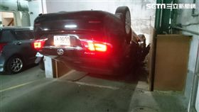 陳女開車欲進入停車場時,不慎誤踩油門導致暴衝,撞上前方閘門後180度往前翻,墜落至6公尺深的地面,所幸並未受傷。(翻攝畫面)