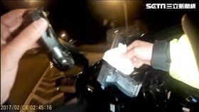 謝男開車行經基隆路遭遇警方盤查,他氣定神閒卻逃不過警員法眼,一舉從駕駛座及外套口袋搜出兩把制式手槍(翻攝畫面)