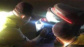 員警蹲地拿手電動照著電動車,被詹姓網友認為是在找排氣管。(圖/翻攝畫面)