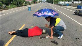 7旬老翁車禍倒地,員警撐傘替他遮陽等待救護車到場。(圖/警方提供)