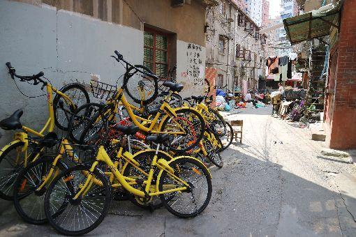 摩拜單車ofo小黃車堆疊路邊中國大陸市占率加起來逾9成的摩拜單車和ofo小黃車在歷經燒錢的終極PK後,終於傳出要合併了。圖為摩拜單車(橘色)與ofo小黃車(黃色)在上海一處社區內堆疊的照片。中央社記者陳家倫上海攝 106年10月3日