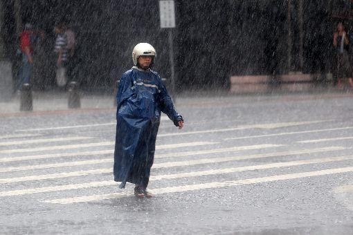 台北大雨(3)中央氣象局12日上午8時左右發布豪雨特報指出,東北風及熱帶性低氣壓外圍雲系影響,大台北地區有局部大雨發生的機率。西門町降大雨,民眾乾脆穿雨衣戴安全帽過馬路。中央社記者吳家昇攝  106年10月12日