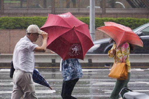 氣象局發布豪雨特報(2)東北風與輕颱卡努產生共伴效應,13日台灣東半部、北部、南部都易有強降雨,中央氣象局上午發布8縣市大雨及豪雨特報,包括宜蘭、台北市部分地區上午累積雨量都已破百毫米,市區起強風並下起大雨。中央社記者裴禛攝  106年10月13日