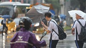 強風吹 傘開花卡努颱風外圍雲系及東北季風共伴效應影響,全台各地出現強風豪雨。有學生13日傍晚走在台北街頭,一陣強風突然把雨傘吹開花,令人措手不及。中央社記者徐肇昌攝 106年10月13日
