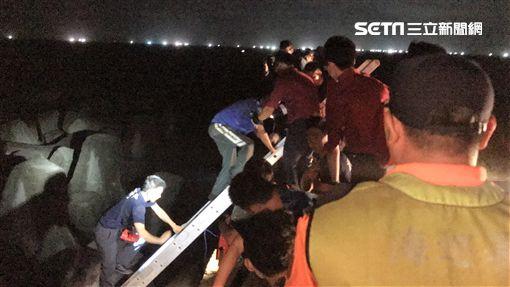 「新德溢12號」漁船出海捕螃蟹,遭海浪打上八尺門漁港防坡堤,張姓船長發射信號彈求援,岸巡及消防人員前往協助,並架設雙節梯助張男脫困。(翻攝畫面)