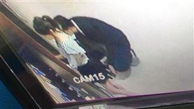 西裝男蹲在地上,拿手機伸到徐女裙底偷拍。(圖/翻攝畫面)