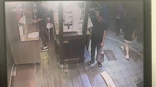 男子伸手進入攤內拿走裝有8千元的信封袋。(圖/翻攝畫面)