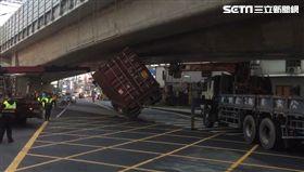 屏東潮州介壽路往東港方向發生一起意外,一輛大型貨櫃車在經過橋底時,竟然卡在橋下,車身還呈現傾斜約45度。貨櫃車司機無奈嘆,「我太遵守交通規則才會卡住啦!」目前已經找來吊車處理現場情況。(圖/翻攝畫面)
