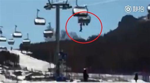 昨(13)日大陸河北有一名7歲男童搭高空纜車時,不小心從椅子跌落,男童緊抓纜車在空中隨風擺盪,相當危險,所幸男童最後墜落雪堆中,沒有生命危險。對此,工作人員則表示,男童父母「不負責」,沒將孩子顧好。(圖/翻攝自秒拍)