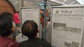 北韓民眾在公告欄看勞動新聞報。(圖/翻攝維基百科)