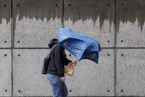 全台留意較大雨勢(2)中央氣象局預報員程川芳表示,28日鋒面通過,大台北地區午後易有較大雨勢發生,降雨範圍也會慢慢擴大,預計晚間雨勢才會趨緩。圖為台北街頭民眾撐傘遮擋雨勢及強風。中央社記者吳家昇攝 107年2月28日