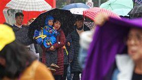 北台灣濕冷(2)中央氣象局預報,22日受大陸冷氣團及華南雲雨區東移影響,北部、東北部濕冷,其他地區有局部短暫雨。台北市區下午雨勢不小,台北101大樓外的觀光客趕緊抱起孩子撐傘避雨。中央社記者裴禛攝 107年2月22日