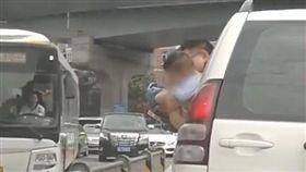 危險!車子移動中 男孩被抱出車外「懸空」小便(圖/翻攝自封面新聞)