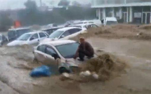 男子爬上引擎蓋,連人帶車被雨水沖走。(圖/翻攝ABC NEWS)