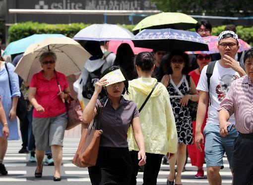 天氣炎熱  民眾遮陽(2)受到太平洋高壓籠罩影響,全台17日仍屬高溫炎熱的天氣,民眾紛紛撐起陽傘,或拿手中物品遮陽。中央社記者張皓安攝  107年5月17日