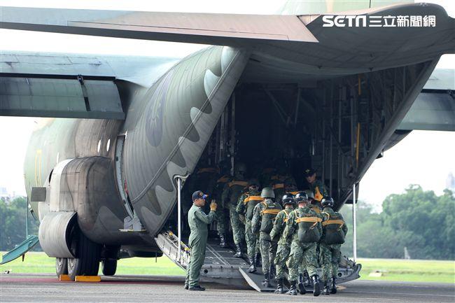 傘兵學員揹著降落傘整齊劃一步伐登機。(記者邱榮吉/屏東拍攝)