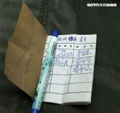 傘連摺傘人員將傘具摺好後,必須在這本筆記簿簽上自己的名字放入傘具裡,以便為這傘具負責。(記者邱榮吉/