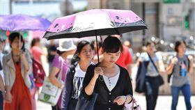 氣溫飆高 街頭熱難耐中央氣象局觀測,台北市27日氣溫飆到攝氏38.2度,是今年全台新高溫,上一次5月最高溫是1991年的37.7度,時隔27年,台北氣溫再創5月新高。圖為台北市街頭民眾用傘遮陽。中央社記者王飛華攝 107年5月27日
