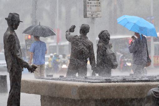 台北傾盆大雨(2)中央氣象局表示,受低壓帶影響,10日起全台天氣趨向不穩定,13至16日西南風增強並持續帶來南方水氣,應慎防局部大雨。台北市10日下午降下大雨,街頭民眾撐傘擋雨。中央社記者吳翊寧攝  107年6月10日