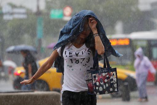 台北傾盆大雨(3)中央氣象局預報,10日起受低壓帶影響,天氣趨向不穩定,並提醒未來幾天全台應慎防局部大雨。台北街頭10日午後降下大雨,有民眾不及躲避,先以外套遮頭擋雨。中央社記者吳翊寧攝 107年6月10日