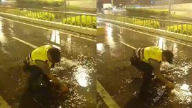 警員在雨中的大馬路上,徒手清理地下道排水孔。(圖/翻攝李孟諺臉書)