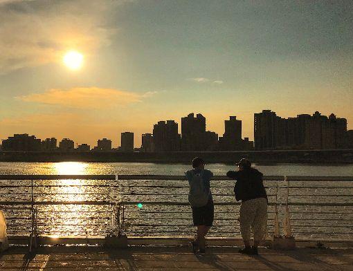 北部高溫(1)中央氣象局2日表示,中南部對流非常旺盛,中午過後持續發布10縣市大雨、豪雨及大豪雨特報;不過北部卻是高溫晴朗,下午大台北地區一度出現攝氏37度高溫,台灣南北天氣形成強烈對比。圖為北市民眾傍晚到河濱公園休憩賞夕陽。中央社記者裴禛攝 107年7月2日