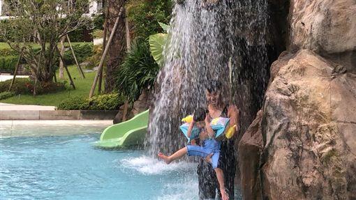 ▲黑人抱起兒子在水柱下沖水。(圖/翻攝自臉書)