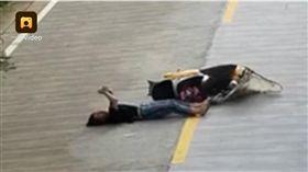 中國大陸一名女騎士摔車後竟直接躺在地上滑手機,車禍(圖/翻攝自梨視頻)