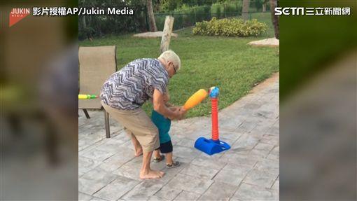 阿嬤耐心扶著孫子的雙手,教導揮棒。