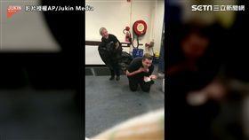 男子受同事驚嚇,摀著胸腿軟趴跪在地。