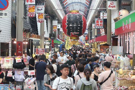 日本黑門市場迎萬名遊客 與在地共存共榮日本「黑門市場」位於西日本最大的城市大阪市,與大阪繁華街區心齋橋、道頓堀連成一片觀光鬧區,人潮絡繹、生氣勃勃,無論是新鮮的漁獲蔬果甚至外帶熱食,都能在主幹道約350公尺長的商店街一網打盡。中央社記者徐肇昌攝 107年7月22日