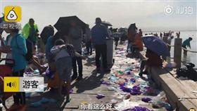 大陸青海烏蘭縣「天空之鏡」茶卡鹽湖,被《中國國家地理》評為一生必去的55個地方,但參觀的遊客非常沒公德心,竟無視垃圾桶,將穿過的鞋套遍地亂扔,導致景區工作人員每日要工作13小時清理垃圾。(圖/翻攝自梨視頻)