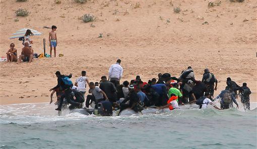 義大利採取強硬拒收難民的政策後,西班牙成為最多難民選擇前往的歐洲國家。日前西班牙塔里法(Tarifa)天體沙灘,就有30多名難民搭橡皮艇搶攤登陸,當時有不少遊客在沙灘裸曬日光浴,直擊難民登陸逃竄,全都看傻眼。(圖/路透社/達志影像)