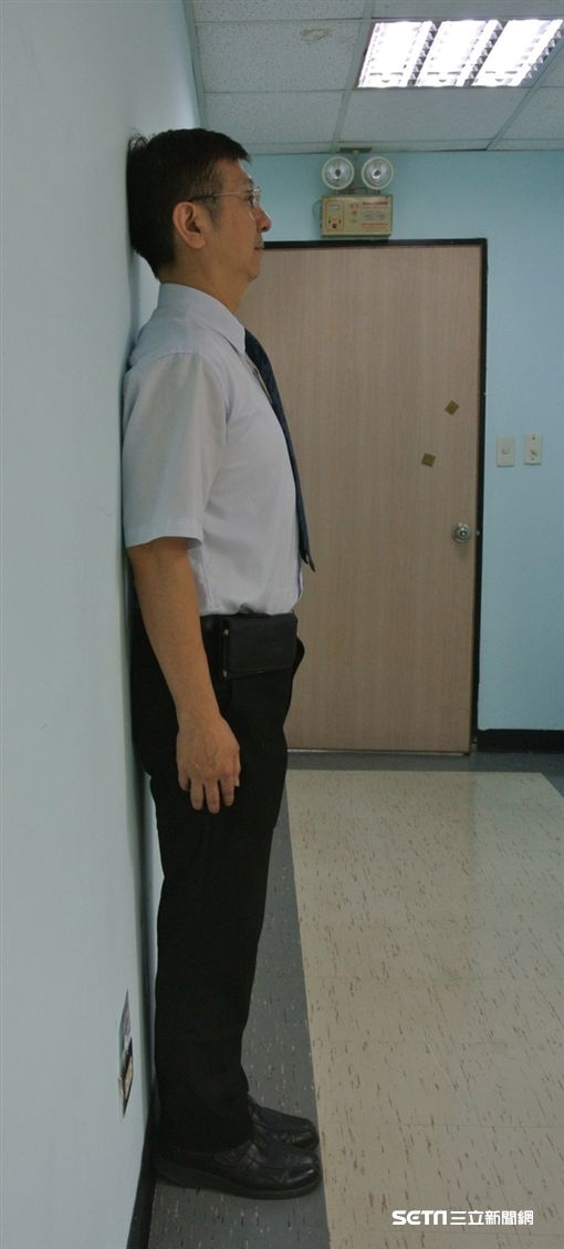 醫師武俊傑示範靠牆站立有助預防烏龜頸。(圖/台北市立聯合醫院提供)
