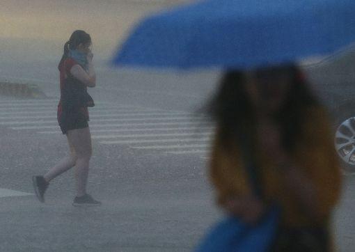 台北雨好大(2)中央氣象局8日下午將北北基和高屏的大雨特報提升為豪雨特報,提醒民眾外出留意。台北市區午後降下大雷雨,有民眾未備雨具,雨中前行。中央社記者張新偉攝 107年9月8日