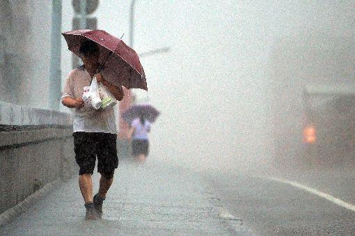 雨勢加劇(1)對流雲系發展旺盛,由於雨勢加劇,中央氣象局8日下午將北北基升為豪雨特報,提醒民眾留意雷擊及強陣風。圖為台北街頭民眾將傘斜撐,遮擋雨勢。中央社記者孫仲達攝 107年9月8日