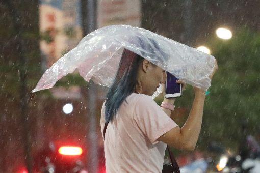民眾用塑膠袋擋雨對流雲系發展旺盛,中央氣象局8日對北北基和高屏發布豪雨特報。傍晚台北市大雨傾盆、雨勢驚人,有民眾拿著塑膠袋擋雨。中央社記者吳翊寧攝 107年9月8日