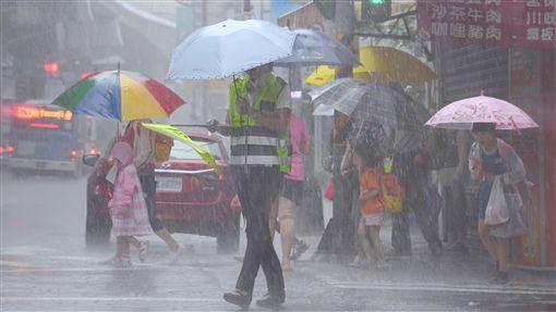 北市午後陣陣大雨中央氣象局10日預報,受熱帶性低氣壓及外圍環流影響,北部及東半部整天會有陣雨或雷雨,並有局部大雨或豪雨。台北市午後下起陣陣大雨,放學的小學生撐傘過馬路。中央社記者王飛華攝 107年9月10日 ID-1542894