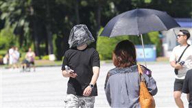 台北天氣好熱(2)中央氣象局預報,受太平洋高壓影響,19日白天各地多雲到晴,北部高溫可達攝氏35、36度以上,台北市上午豔陽高照,民眾用隨身衣物蓋住頭部擋陽光。中央社記者謝佳璋攝  107年9月19日