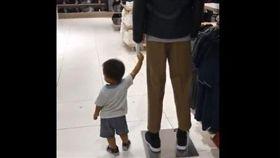 小朋友緊牽展示模特兒的手不放。(圖/翻攝自Twitter)