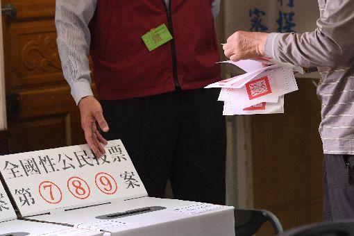 九合一選舉併公投登場(2)107年地方公職人員選舉及全國性公民投票案第7案至第16案24日投開票,一早就有不少民眾前往投票所,分別領取選舉票與公投票進行投票。中央社記者孫仲達攝 107年11月24日